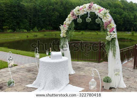 Vintage stylish wedding aisle with a white floral arch, a lake and a forest in the background - stock photo