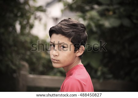 Vintage stylistic portrait of serious thoughtful boy with de-saturated look and vignetting - shot with vintage lens