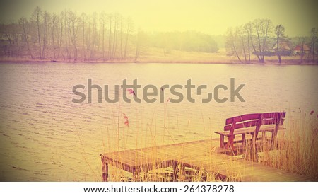 Vintage stylized photo of a wooden bench at the lake. - stock photo