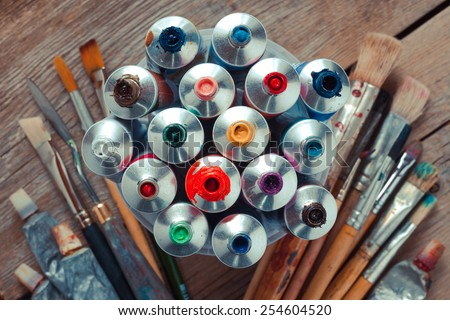 Vintage stylized photo of oil multicolor paint tubes closeup and artist paintbrushes on wooden desk. Top view. - stock photo