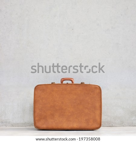vintage suitcase and blank concrete background - stock photo