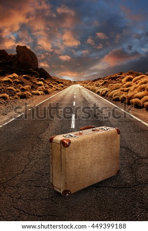 Vintage suitcase in the middle of a grungy asphalt road leading through desert landscape - stock photo