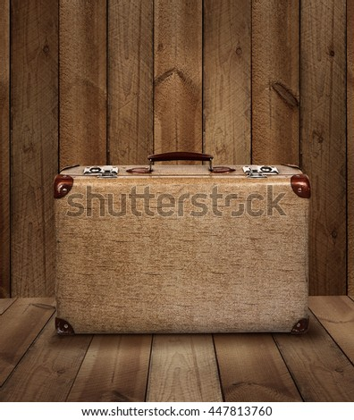 Vintage suitcase on rough wooden plank background - stock photo