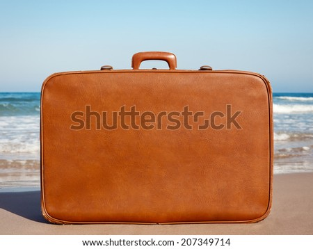vintage suitcase on the beach - stock photo