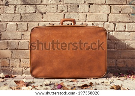 vintage suitcase on the street and bricks background - stock photo