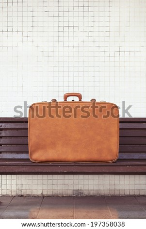 vintage suitcase on the street on the bench - stock photo