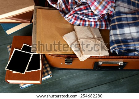 Vintage suitcase open with clothes and books on wooden background - stock photo