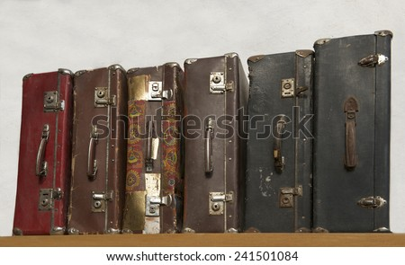 Vintage suitcases on a desk, 6 suitcases on a row, vintage photo of old travel suitcases with stickers, voyage, old antique suitcase, baggage - stock photo