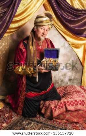 Vintage sultan character with turban bringing a full treasure chest - stock photo