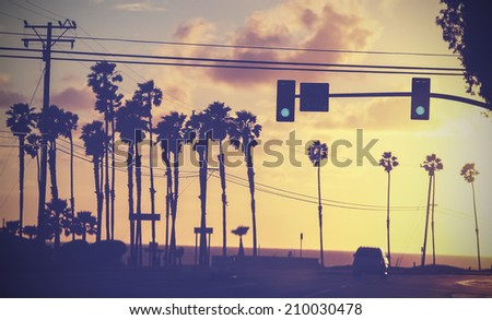 Vintage sunset picture of palms and poles on street against sun. - stock photo