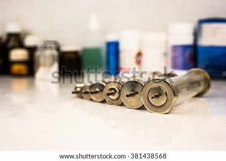Vintage syringes with glass vials and medications pills, drugs in background - stock photo