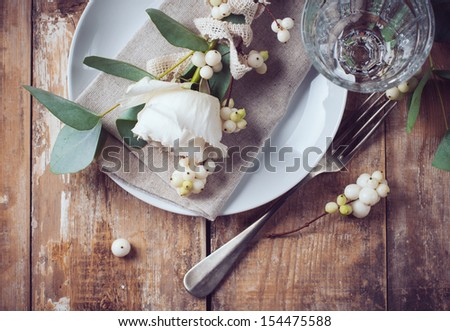 Vintage table setting with floral decorations, napkins, white roses, leaves and berries on a wooden board background - stock photo