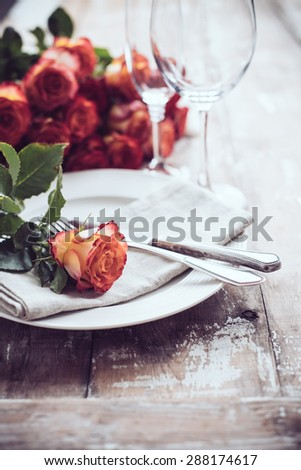 Vintage table setting with glasses and cutlery on an old wooden board, wedding table decor