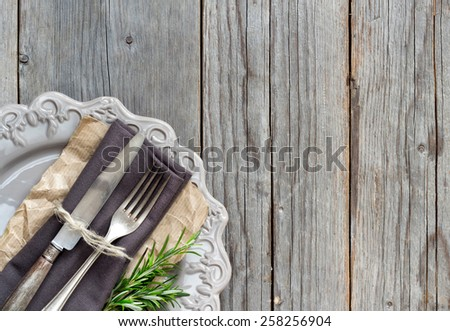Vintage Table setting with napkin and plate on old wooden table - stock photo