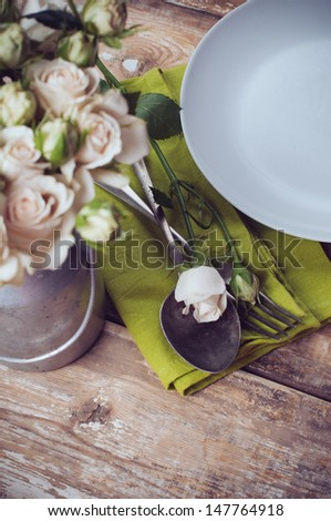 Vintage table setting with rose flowers on a linen napkin on a wooden board background, close-up - stock photo
