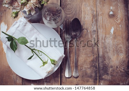 Vintage table setting with roses, antique rustic dishes and cutlery on the wooden background, close-up - stock photo