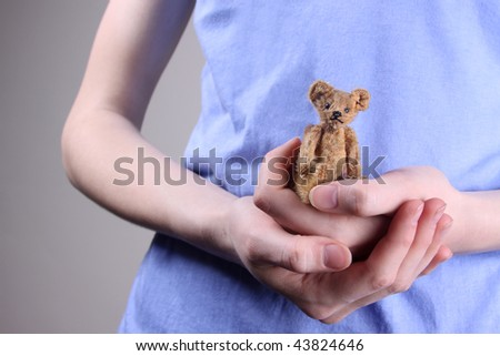 Vintage teddy bear held in woman's hands. - stock photo