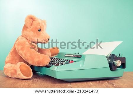 Vintage Teddy Bear toy and retro old typewriter - stock photo