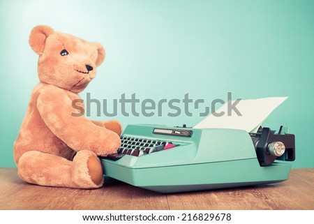 Vintage Teddy Bear toy and retro old typewriter with paper blank front mint green background - stock photo
