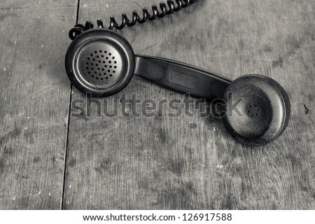 Vintage telephone handset on old wooden table background - stock photo