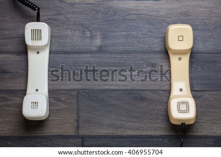 Vintage telephone handset on wooden table - stock photo