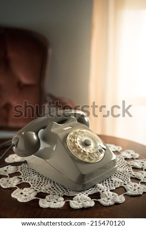 Vintage telephone on doily and wooden table in the living room. - stock photo