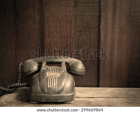 Vintage telephone on old table sepia still life photo. - stock photo