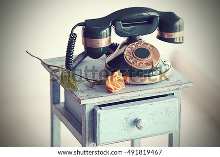 Vintage telephone on rustic blue nightstand