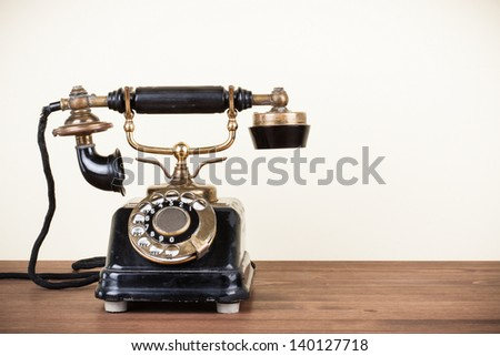 Vintage telephone on wooden table - stock photo