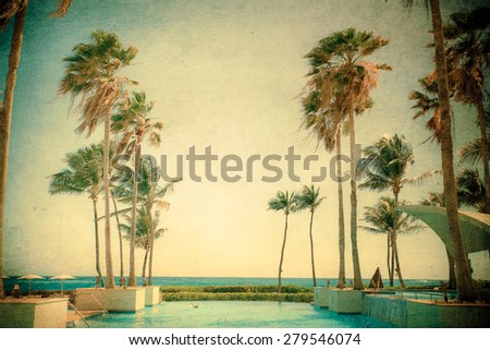Vintage textured beachfront resort pool with tropical palm trees  - stock photo