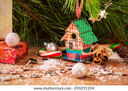 Vintage textured Christmas card with pine, nesting box and christmas gifts over old wooden background. Selective focus. Toned image - stock photo