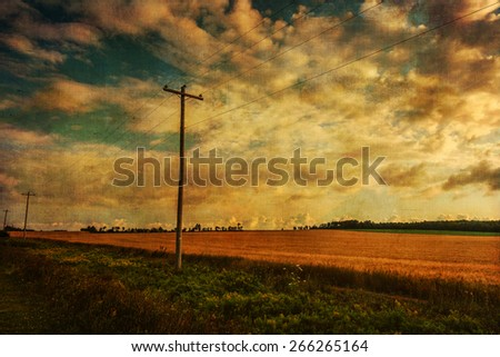 Vintage textured landscape with telephone lines along wheat fields in rural Prince Edward Island.  - stock photo