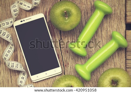 vintage.  The flat position, White smart-phone, ripe green apple, dumbbells and measuring tape on a gray wooden background. Concept: the fashion for a healthy lifestyle   - stock photo