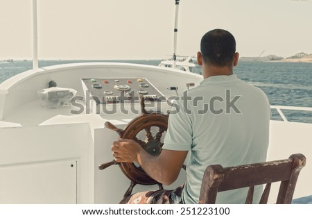 Vintage tinted photo of captain of a yacht sitting by the steering wheel - stock photo