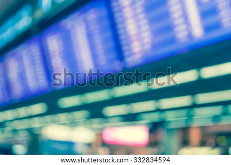 vintage tone blur image of blue screen flight schedules and people in airport for background usage.