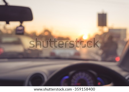 vintage tone blur image of people driving car on day time for background usage.(take photo from inside) - stock photo