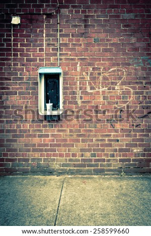 Vintage tone image of brick wall with obsolete payphone
