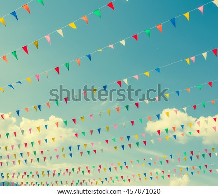 vintage tone image of festival flag line with blue sky in background on day time . - stock photo