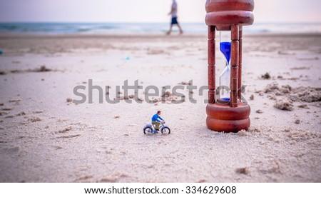 vintage tone image of mini figure dolls biker and sandglass on the beach blur in background. - stock photo
