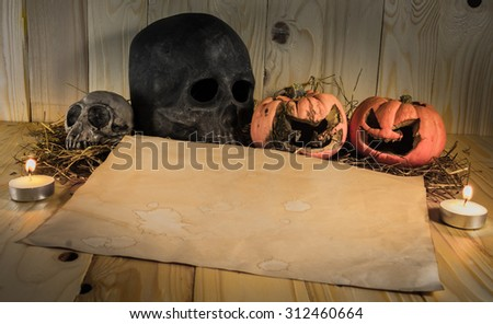 vintage tone image of rotten Halloween pumpkin and old  paper with candlelight and dry grass. Wooden background.