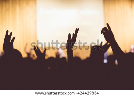Vintage tone of christian music concert with raised hand - stock photo