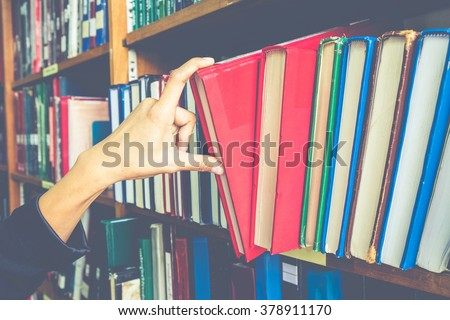 Vintage tone of closeup hand selecting book from a bookshelf(selective focus)  - stock photo