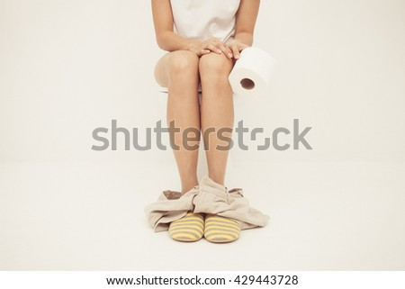Vintage tone of Closeup photo of woman sitting on toilet and using toilet paper - stock photo