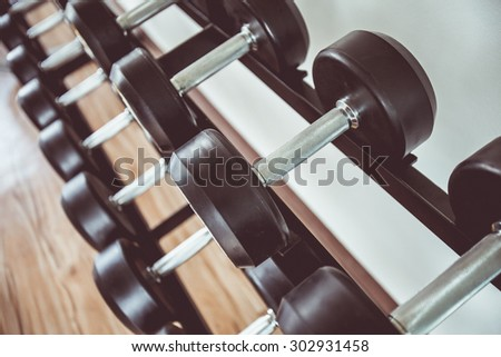 Vintage tone of Dumb bells lined up in a fitness studio. picture is short focus