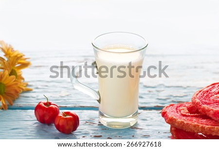 vintage tone of glass milk and red flavored puffed fried, cherry on blue wooden background, soft focus and blur - stock photo