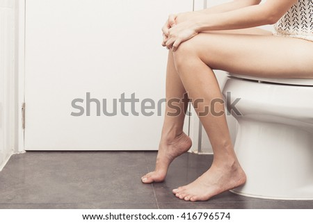 vintage tone of Hand of woman in bath towel sitting on toilet bowl - stock photo