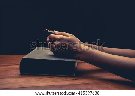 vintage tone of Hands folded in prayer over Holy Bible - stock photo