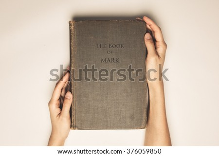 Vintage tone of hands hold the book bible of mark - stock photo