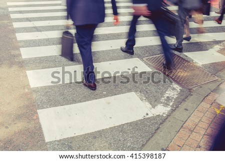 vintage tone of Motion blurred pedestrians crossing street