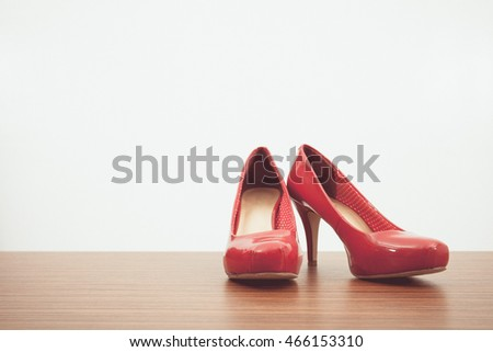 Vintage tone of Pair of woman's red shoes on floor on light wall background